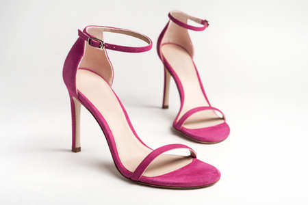 Woman's pink high heels shoes with ankle strap on a white background.