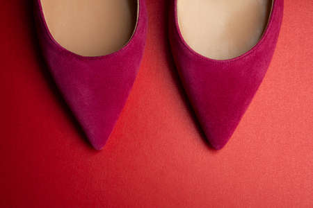 Women's shoes of red fuchsia color on a red background close-up. Abstract fashion.