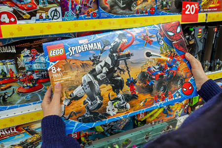 Closeup of box with a Lego constructor in the hands of the buyer. Lego is a popular line of construction toys manufactured by the Lego Group. Minsk, Belarus - March 2021 Publikacyjne