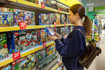 Woman chooses Lego as a gift for a child. Large selection of Lego toys. Lego is a popular line of construction toys manufactured by the Lego Group. Minsk, Belarus - March 2021