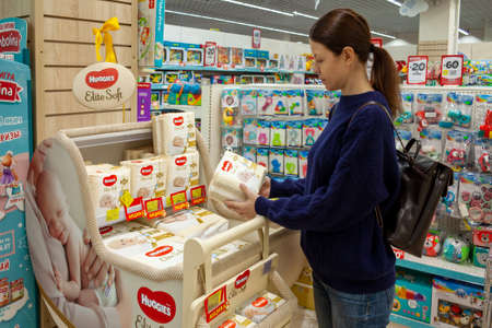 Pregnant woman buys diapers Huggies at the supermarket. Minsk, Belarus - March 2021