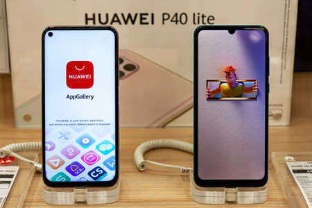 New Huawei mobile smartphones is shown on retail display in electronic store. Close-up look at mobile gadgets, brand logo in the background. Minsk, Belarus - March 2021