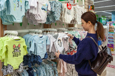 Young pregnant woman choosing newborn clothes at baby shop store Publikacyjne