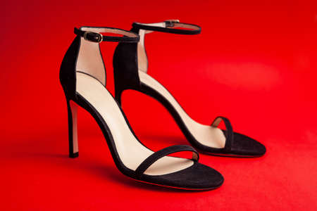 Sexy women black sandals with high-heeled stilettos on a red background.