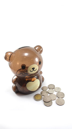 Depositing a coin into a childs teddy bear money box. photo
