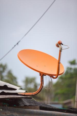 satellite tv: Orange satellite TV receiver on roof Stock Photo