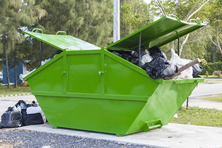 A big pile of garbage in a green container