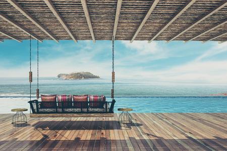 美しいスイング ソファーを提供する装飾用枕し、バルコニー、プール海の景色、ビンテージ トーン 3 d レンダリングでリラックス
