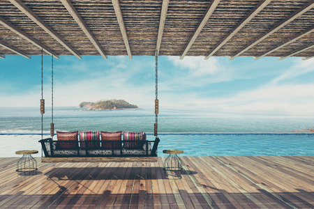 Beautiful swing sofa furnish and pillow for decoration and relax at balcony and pool sea view ,Vintage Tone - 3d rendering Imagens
