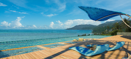 Sea View Andaman sea Beautiful Swimming pool with armchair and wooden floor  - 3d rendering Stock Photo