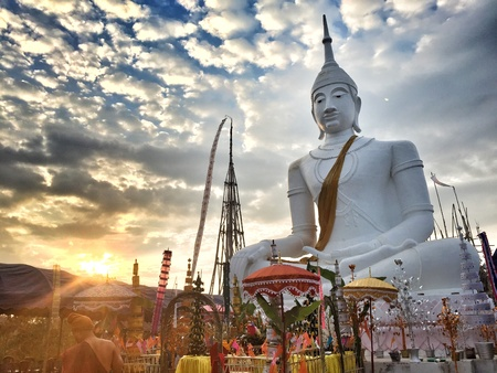 buddha image: Big white buddha image in a ceremony with morning sunlight on the cloudy day