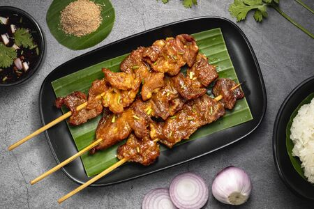 Top view of grilled pork with sticky rice and thai spicy sauce and ingredients. Moo ping is grilled pork in traditional Thai style food. Oily grilled pork will rise cholesterol.