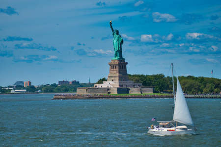yacht in front of the statue of liberty on a sunny summer day