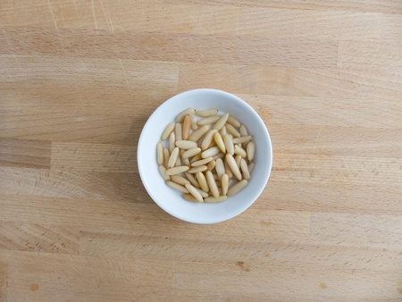 pine nuts: Pine nuts in a bowl on wood