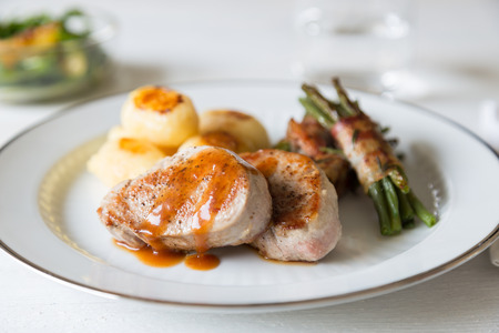 Pork medallions with potatoes and beans wrapped in bacon Reklamní fotografie