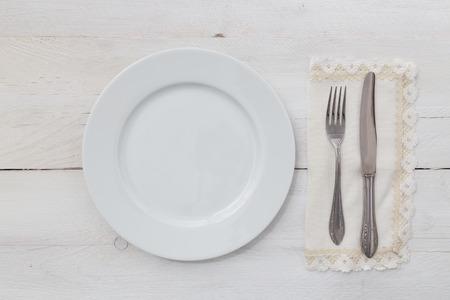 White plates and silverware on a light wood background photo