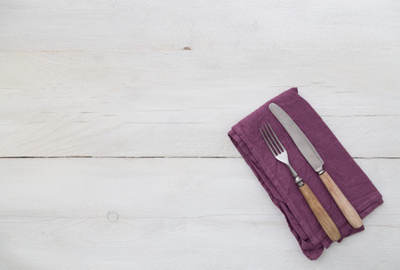 Cutlery and napkin on light wood background photo