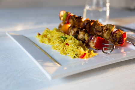 Curry chicken skewers with rice on white plate photo