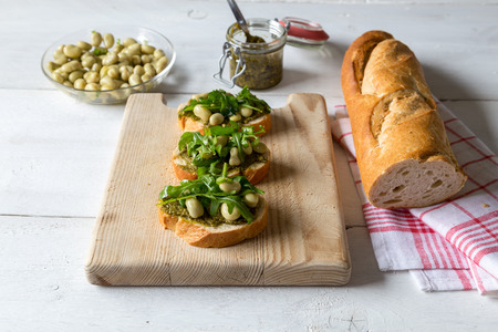 Bruschetta with beans and arugula on a wooden board