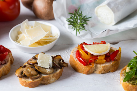trillion: Bruschetta with beans and arugula, mushrooms, goat cheese on a wooden board Stock Photo