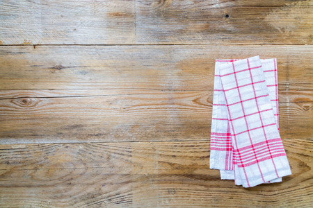Red kitchen towel on rustic wooden background Stock Photo