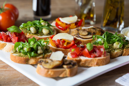 Bruschetta with beans and arugula, mushrooms, goat cheese on a wooden board photo