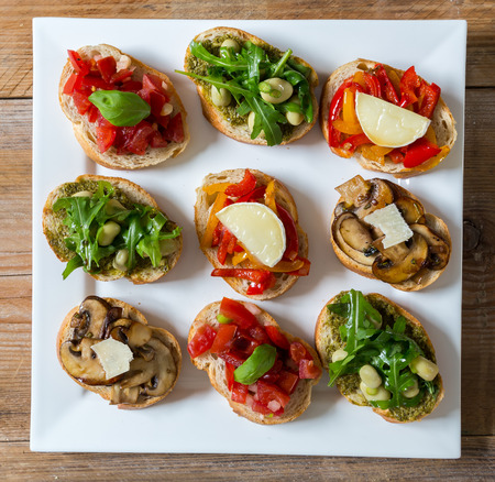 Bruschetta with beans and arugula, mushrooms, goat cheese on a wooden board Standard-Bild