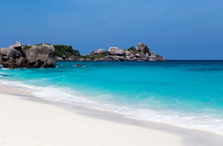arena blanca: Playa de arena blanca y mar azul turquesa, bajo un cielo azul.