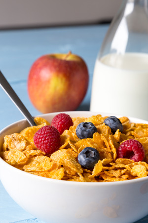 Cornflakes in a bowl with milk and fruits. photo