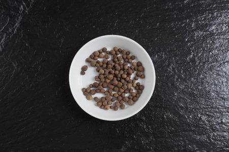 allspice: Allspice in a bowl on a slate.