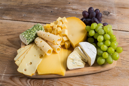 Cheese plate variation on a wooden table. photo