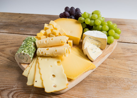 cheese plate: Cheese plate variation on a wooden table.