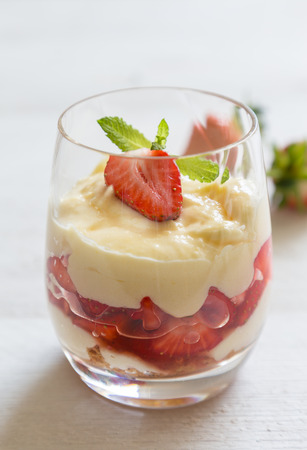 tipsy: Vanilla pudding with tipsy strawberries on wood.