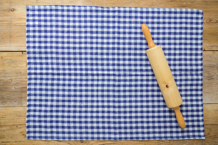 Rolling pin and dishcloth on rustic wooden background. photo