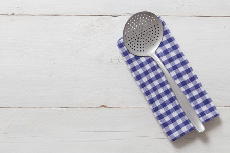 slotted: slotted spoon and kitchen towel on rustic wooden background.