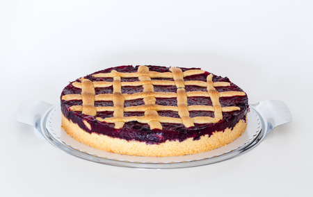 Lattice cake with forest berries against white background.