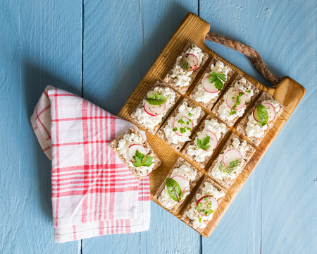 crispbread: Crispbread with cottage cheese radishes and herbs. Stock Photo