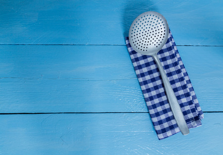 slotted: slotted spoon and tea towel on blue wooden background.