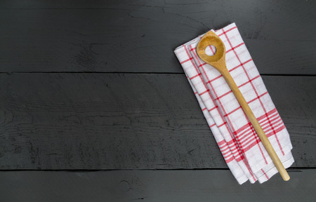 dish cloth: Wooden spoon and dish cloth on black wooden background.
