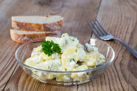 potato salad: Potato salad in a glass bowl on wooden board.
