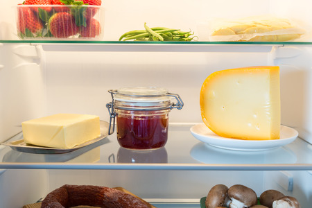 Open fridge filled with food.