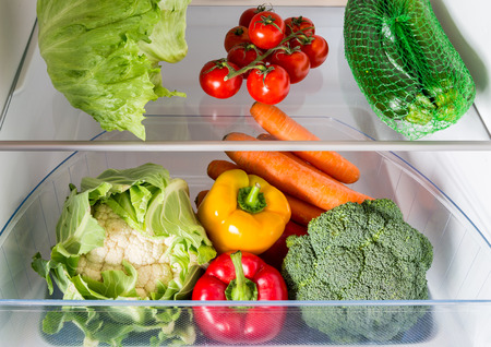 raw vegetables: Open fridge filled with fruits and vegetables.