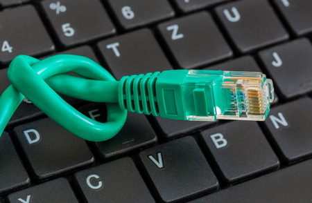 ip address: Network cable with green knot and keyboard. Stock Photo
