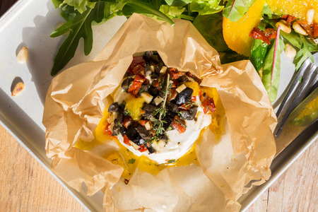 parchment paper: Baked goat cheese Mediterranean in parchment paper.