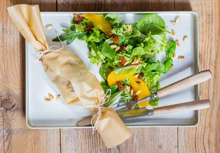 queso de cabra: Queso de cabra al horno Mediterráneo en el papel de pergamino.