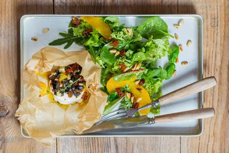 queso de cabra: Queso de cabra al horno Mediterr�neo en el papel de pergamino.