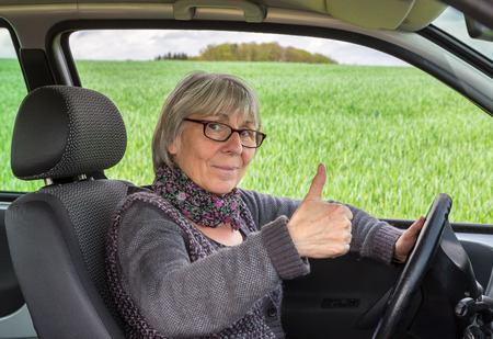 vigorously: Senior Woman in the car with thumbs up. Stock Photo