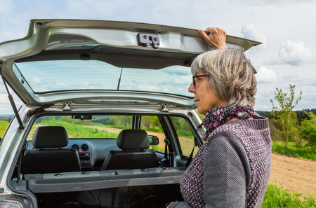 enjoy space: Senior Woman opens the trunk of the car.