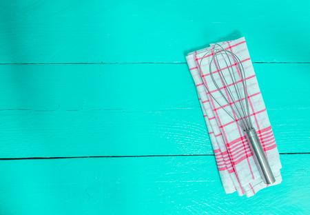 tea towel: Whisk and tea towel on turquoise wooden background.