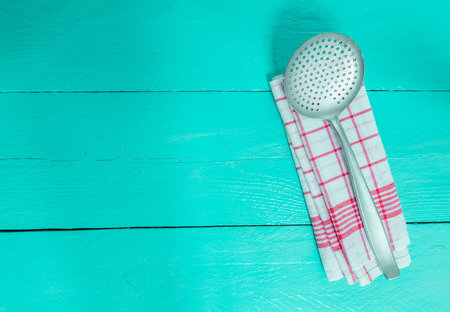 tea towel: slotted spoon and tea towel on turquoise wooden background.